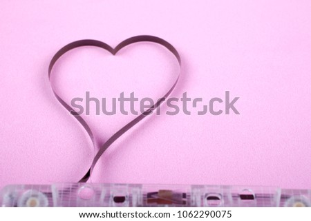 Film in a shape of heart from Compact Cassette. Love for music and songs. Pink background. #1062290075