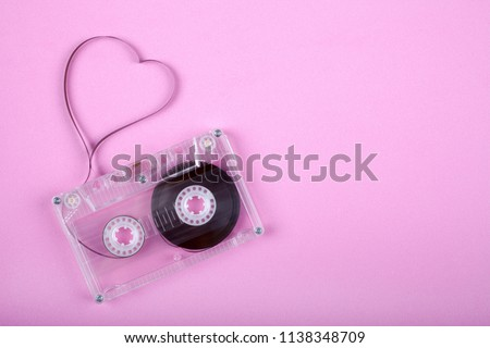 Film in a shape of heart from Compact Cassette. Love for music and songs. Pink background. #1138348709