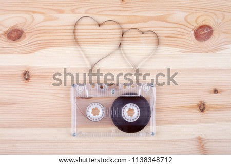 Film in a shape of heart from Compact Cassette. Love for music and songs. Wooden background. #1138348712
