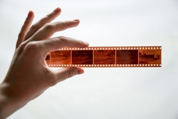 Film photography special envelope slips for negative storage. 35mm and medium format photography. A hand holding a film strip in front of white background.
