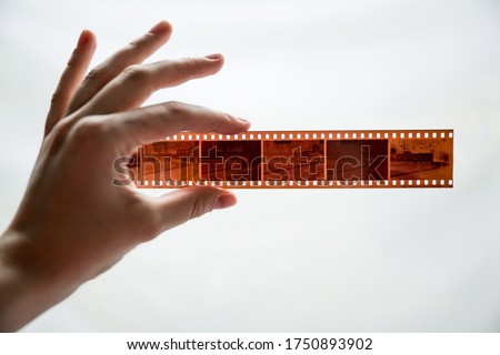 Photo of  Film photography special envelope slips for negative storage. 35mm and medium format photography. A hand holding a film strip in front of white background.