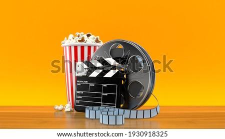 Film reel with popcorn and film slate on orange background. 3d illustration