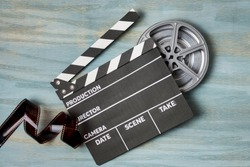 Film stripes with clapperboard and film reel on blue textured background