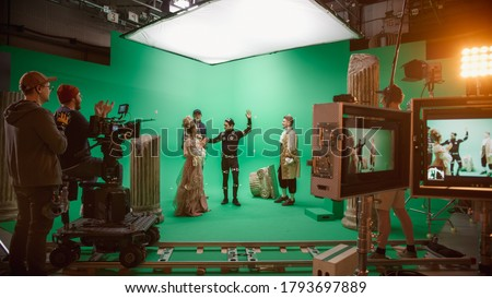 Film Studio Set: Shooting Green Screen Scene with Two Talented Actors Wearing Renaissance Clothes Talking, Director Finishes Scene, Celebrates Success, Embraces Actors. Period Drama Movie Backstage