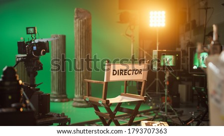Film Studio Set with Focus on Empty Director's Chair. On the Studio Film Set with High End Equipment Professional Crew Shooting High Budget Movie Сток-фото ©