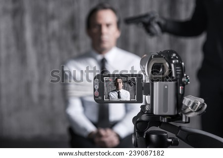 Filming hostage. Tied up businessman caught by a criminal sitting in front of a dirty wall with gun near his head while video camera filming it on the foreground