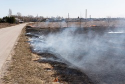 Filming of burning and scorched dry fields near the villages. Dry grass burns in the field, and after the fire, the ground is covered with black ash. The death of nature due to human influence.