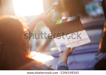 Filming on location. Woman holding a clapperboard in front of the camera, the filming process. Scene on location.