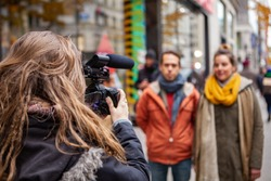 Filmmaker captures video in city center. An over the shoulder view of a female videographer filming a man and woman on a busy urban street for a documentary, with copy-space on the right.