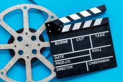 Filmmaker profession with clapperboard and video tape on blue background top view