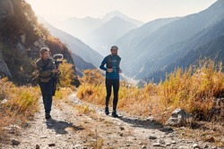 Filmmaker shooting documentary about runner athlete on the wild trail at mountains