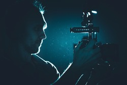 Filmmaker with Modern DSLR Video Camera Taking Shot in a Dark. Making Documentary Film. Professional Videography Equipment.