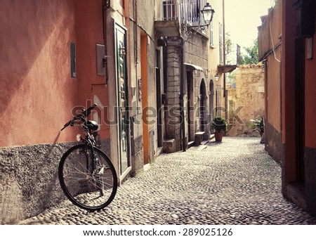 stock photo filtered image of a bicycle on the narrow street of bellagio town at the famous italian lake como 289025126 - Каталог — Фотообои «Улицы, переулки»