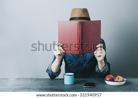 filtered photo of a young hipster man reading a book and relaxing #331940957