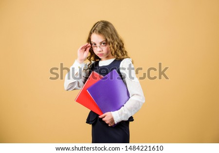 Final exam coming. Girl hold textbook folder test. School exam concept. Prepare for exam. Preparing to exams in library. Small child formal wear. Formal education and homeschooling. Check knowledge. #1484221610