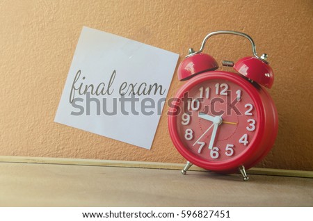 Final Exam prepared week Final Exam text on paper memo at orange wall with red clock #596827451
