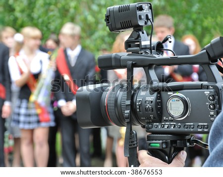 Final examinations. School-leaving party (graduation party).Operator recording a holiday on a video camera.