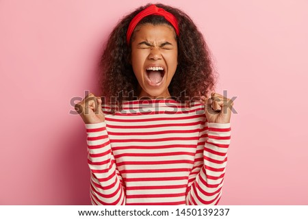 Finally success. Joyful curly young woman clenches fists with triumph, rejoices winning expensive prize, exclaims with joy, wears red headband and striped jumper, isolated on pink background