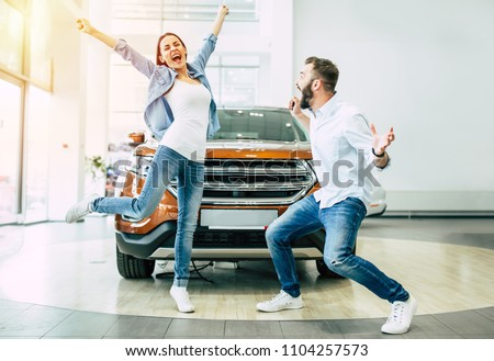 Finally we bought a car. Happy young couple chooses and buying a new car for the family in the dealership.