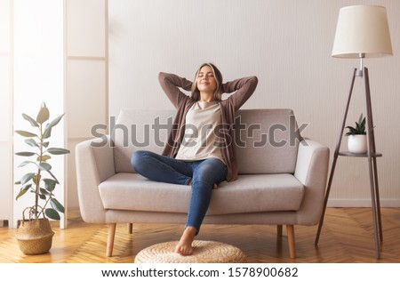 Finally weekends. Millennial girl relaxing at home on couch, enjoying free time, empty space Foto stock ©