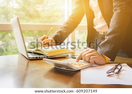 finance,accounting,Businessman analyzing investment charts with calculator laptop calculate technology in office,business, concept,selective focus,vintage color