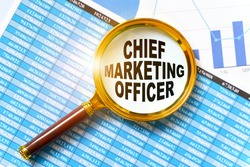 Finance and business concept. Financial reports, charts and a magnifying glass are on the table. Inside the magnifier there is an inscription - CHIEF MARKETING OFFICER