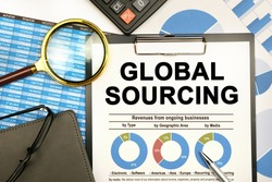 Finance and business concept. The businessman has on his desk graphs with reports, a notebook, a magnifying glass and a document with the inscription - GLOBAL SOURCING