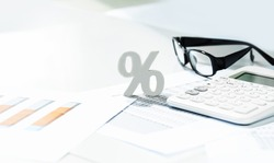 Finance and business concept. White calculator and percentage sign on financial graphs on office desk, paperwork binder, glasses. Accounting budgeting or market analysis. Web banner with copy space