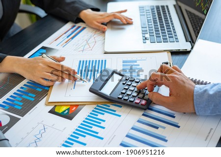 Finance business people or accountants point to the graph and use a calculator to calculate company income, expenses, taxes, and employee bonuses for Next year's improvement plan Stock foto ©