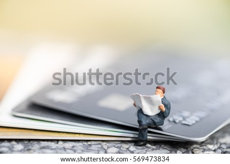Finance, Business, Shopping and e-commerce concept. Close up of businessman miniature figure toy sit and read newspaper on stack of credit cards #569473834