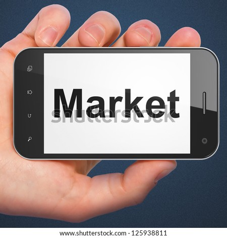 Finance concept: hand holding smartphone with word Market on display. Generic mobile smart phone in hand on Dark Blue background.