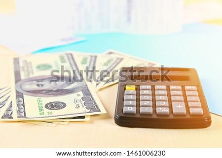 Finance concept. The United States hundred-dollar bills , calculator , bills