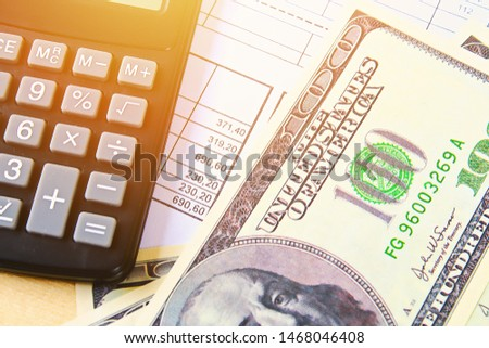 Finance concept. The United States hundred-dollar bills , calculator , bills.