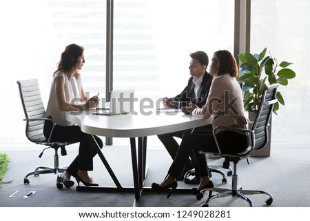 Finance manager negotiating with multiracial mixed race and middle eastern ethnicity investors sitting at desk boardroom discussing new projects share information and planning future collaboration