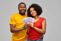 finance, saving and people concept - happy smiling african american couple with euro money over grey background