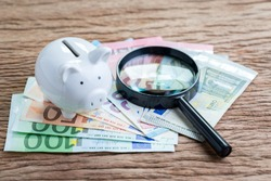 Finance saving, tax or searching for yield concept, white piggy bank with magnifier glass on pile of Euro banknotes on wooden table, transparency of the European Union government economics idea.
