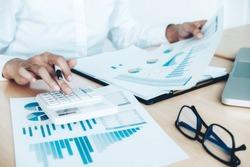 Finances Saving Economy concept. Female accountant or banker use calculator.