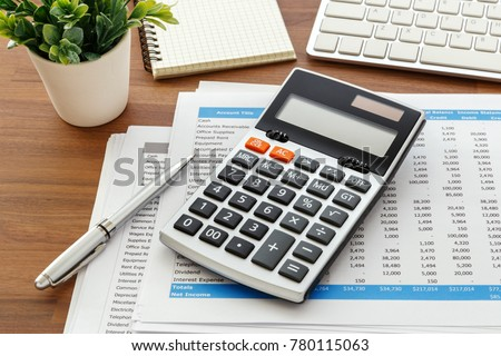 Financial accounting with calculator and accounting  data on wooden table