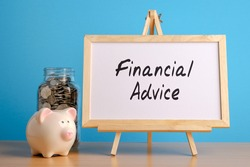 Financial Advice, financial concept. Mason jar with coins inside, piggy bank and whiteboard on wooden table.