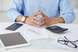 Financial adviser sitting among sheets with statistics