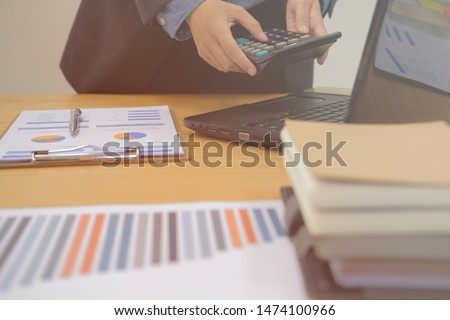 financial adviser working with calculator at office. accountant doing accounting & calculating revenue & budget. bookkeeper making calculation. finance & economy concept