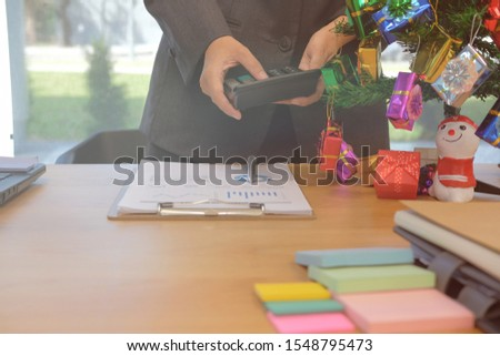 financial adviser working with calculator at office. accountant doing accounting & calculating revenue & budget. bookkeeper making calculation during christmas new year holiday