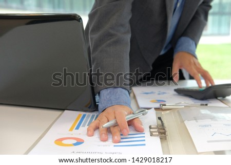 financial adviser working with calculator, business document at office. accountant doing accounting & calculating revenue & budget. bookkeeper making calculation. finance & economy concept