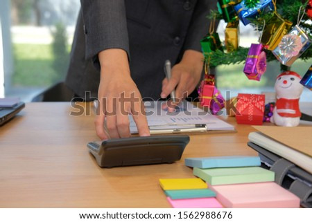 financial adviser working with calculator, business document at office. accountant doing accounting & calculating revenue & budget. bookkeeper making calculation during christmas new year holiday