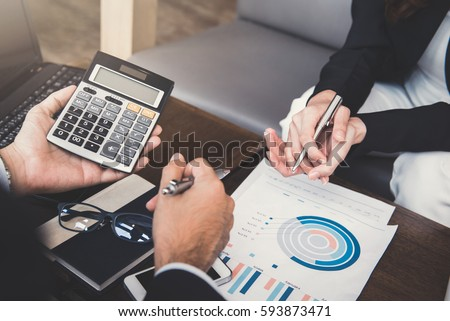 Financial adviser working with client, calculating and analyzing data at the table in cafe