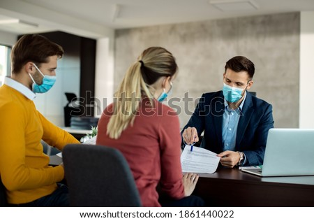 Financial advisor and a couple going through paperwork while having a meeting during coronavirus pandemic.