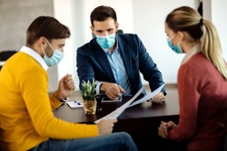 Financial advisor going through paperwork with a couple in the office and wearing face mask due to COVID-19 pandemic.