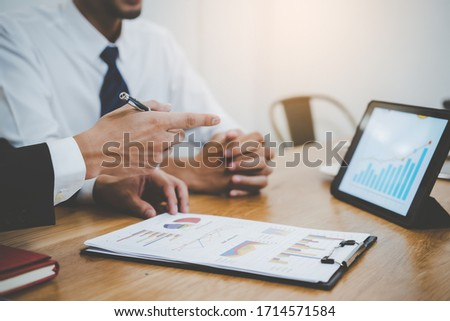 financial advisory services. Asian advisor showing plan of investment to clients in the consultancy office. Stock photo ©