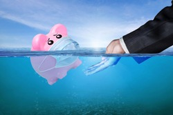Financial Aid and rescue from debt problems for investments above water as a drowning pink piggy bank sinking in blue water. Concept of financial crisis after coronavirus covid-19 pandemic.