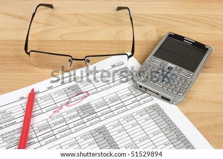 Financial analysis - income statement, red pen, glasses and a smart phone